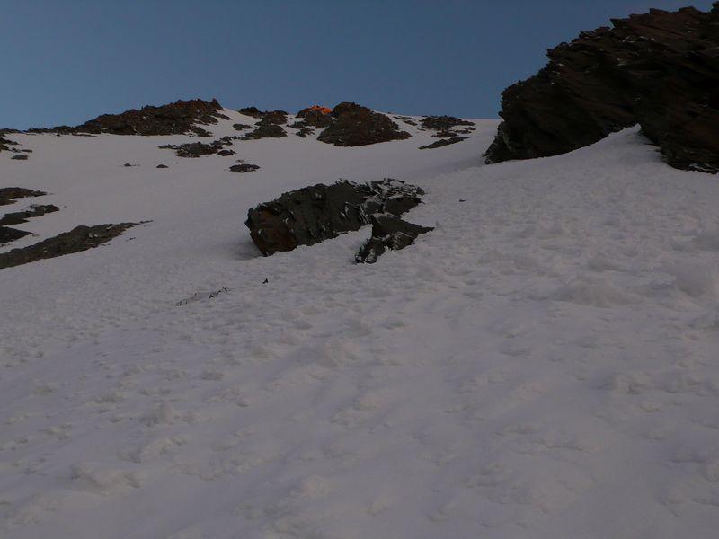 Parte final de la pendiente de nieve y primeras luces sobre el collado a 3900 metros